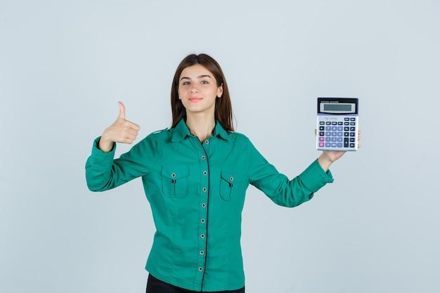 Młoda dama trzyma kalkulator, pokazuje kciuk w zielonej koszuli i wygląda wesoło. przedni widok.