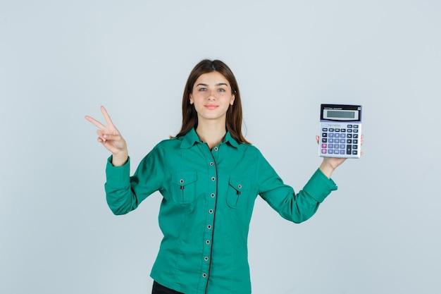 Młoda dama trzyma kalkulator, pokazuje znak v w zielonej koszuli i wygląda dumnie. przedni widok.