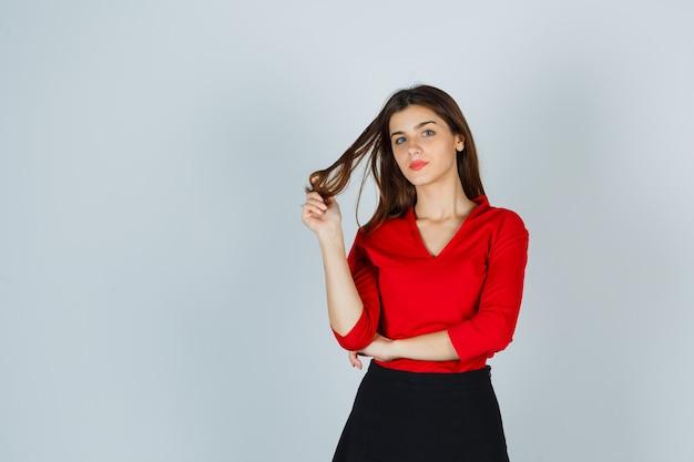 Młoda dama trzyma kosmyk włosów, pozując w czerwonej bluzce, spódnicy i wyglądającej olśniewająco