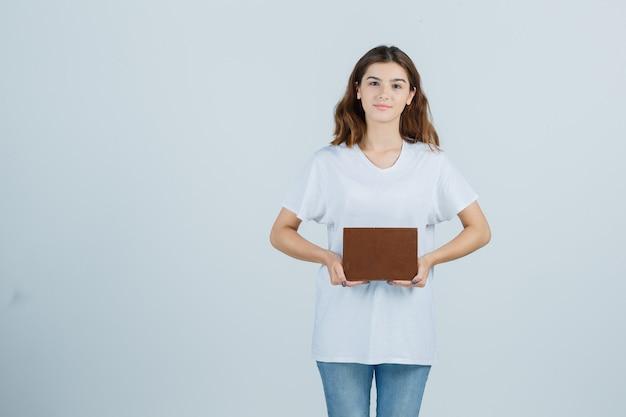 Młoda dama trzyma książkę, patrząc na kamery w t-shirt, dżinsy i patrząc pewnie. przedni widok.