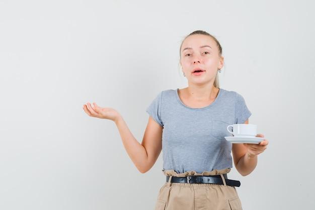Młoda dama trzyma kubek napoju w t-shirt, spodnie i wygląda zdziwiona. przedni widok.