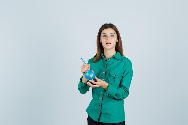 Młoda dama trzyma kulę ziemską i wskazując na nią w koszuli i patrząc skoncentrowany. przedni widok.