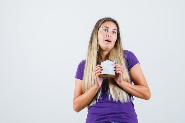 Młoda dama trzyma model domu w fioletowej koszulce i wygląda na zaskoczoną. przedni widok.