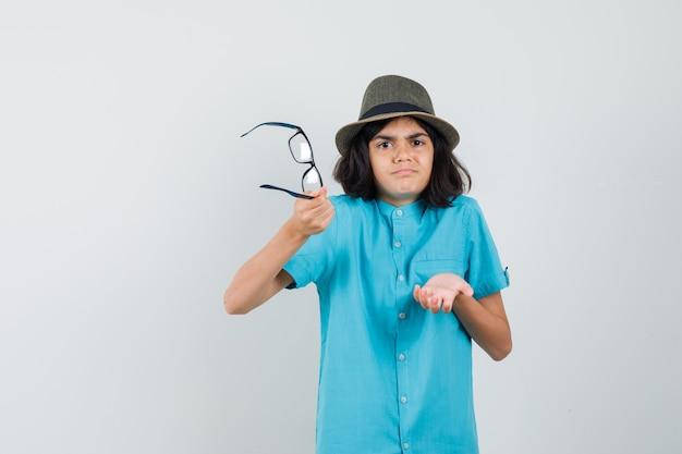 Młoda dama trzyma okulary w niebieskiej koszuli, kapeluszu i wygląda bezradnie