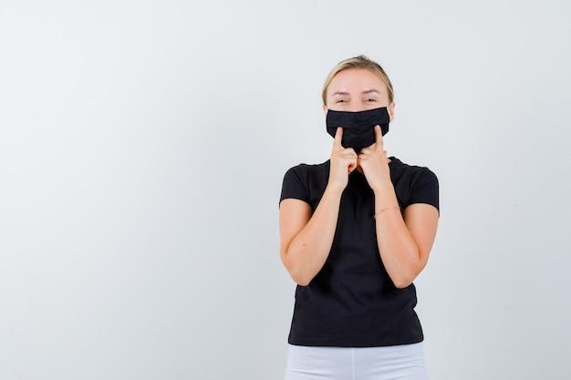 Młoda dama trzyma palce na jej masce medycznej w czarnej koszulce i wygląda wesoło, widok z przodu.