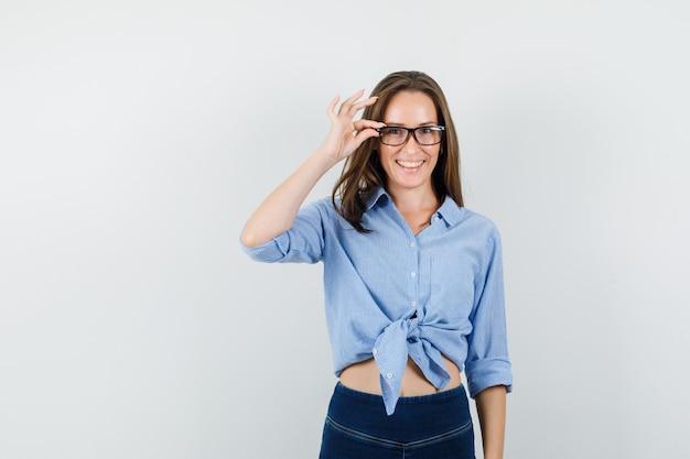Młoda dama trzyma palce na jej okularach w niebieskiej koszuli, spodniach i wygląda optymistycznie