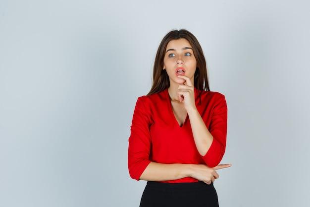 Młoda dama trzyma palec na wardze w czerwonej bluzce, spódnicy i wygląda zdziwiona