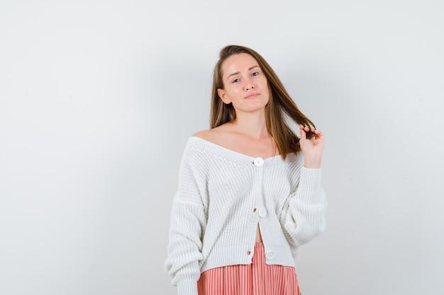 Młoda dama trzyma pasmo włosów w swetrze i spódnicy, patrząc efektownie na białym tle
