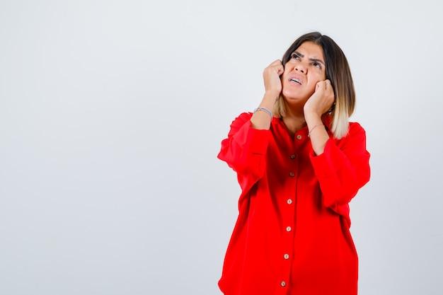 Młoda dama trzyma pięści na policzkach w czerwonej koszuli oversize i wygląda ostrożnie. przedni widok.
