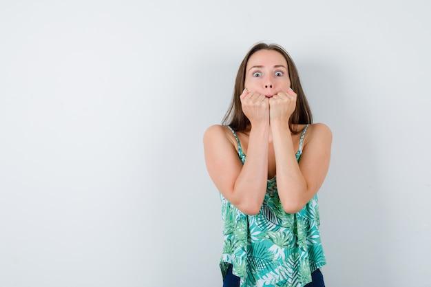 Młoda dama trzyma pięści na ustach i wygląda na przerażoną, widok z przodu.