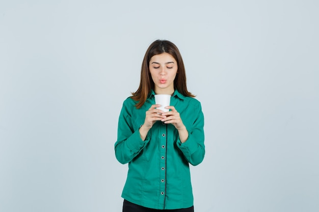 Młoda dama trzyma plastikową filiżankę kawy w koszuli i patrząc skoncentrowany, przedni widok.