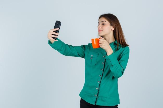 Młoda dama trzyma pomarańczową filiżankę herbaty, biorąc selfie z telefonem komórkowym w koszuli i patrząc pewnie, widok z przodu.