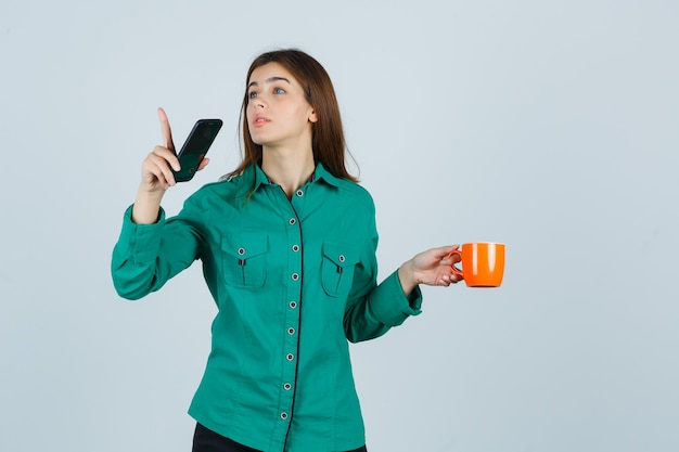 Młoda dama trzyma pomarańczową filiżankę herbaty i telefon komórkowy, wskazując w koszuli i patrząc ostrożnie. przedni widok.