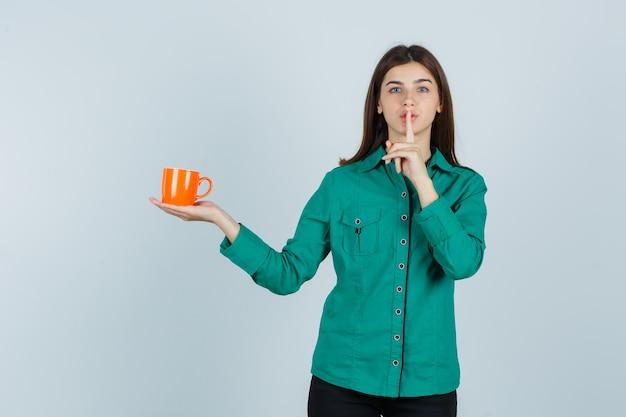 Młoda dama trzyma pomarańczową filiżankę herbaty, pokazując gest ciszy w koszuli i patrząc uważnie. przedni widok.