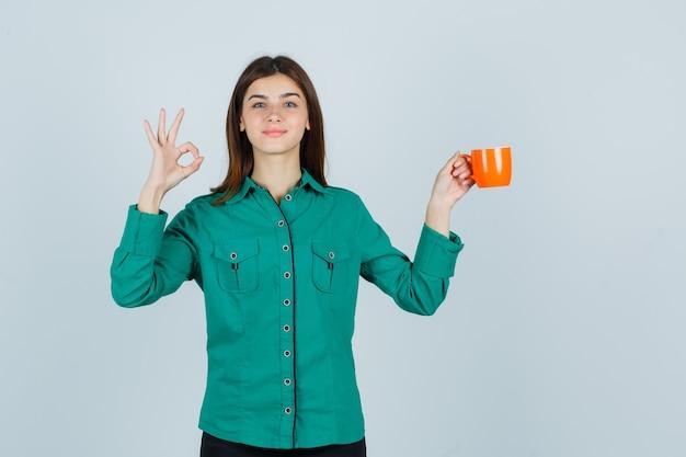 Młoda dama trzyma pomarańczową filiżankę herbaty, pokazując ok znak w koszuli i wyglądająca na pewną siebie. przedni widok.