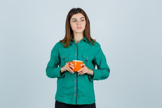 Młoda dama trzyma pomarańczową filiżankę herbaty w koszuli i patrząc skupiony, przedni widok.