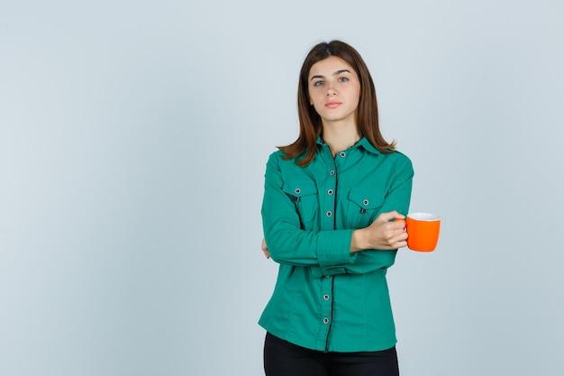 Młoda dama trzyma pomarańczową filiżankę herbaty w koszuli i wygląda pewnie, widok z przodu.