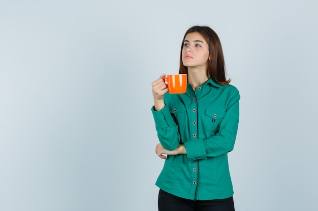 Młoda dama trzyma pomarańczową filiżankę herbaty w koszuli i zamyślony, widok z przodu.