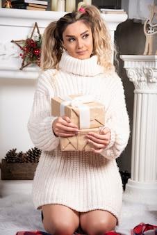 Młoda dama trzyma prezenty przy kominku.