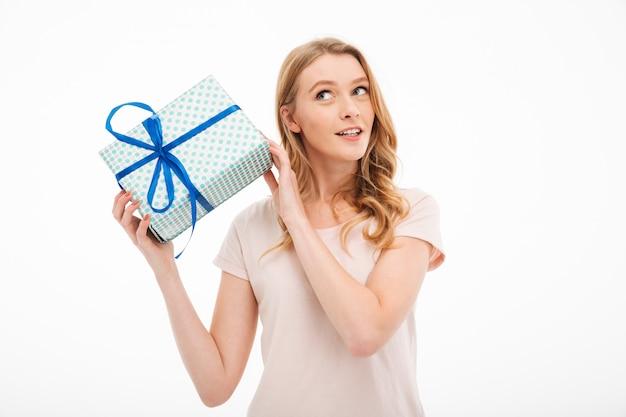 Młoda dama trzyma pudełko niespodzianka.