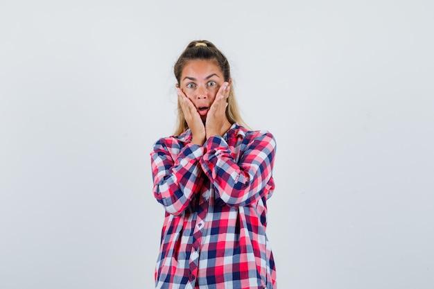 Młoda dama trzyma ręce na policzkach w kraciastej koszuli i wygląda na zaniepokojoną. przedni widok.