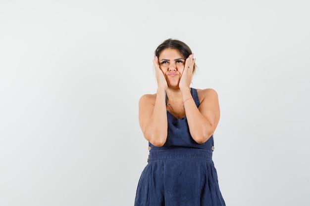 Młoda dama trzyma ręce na policzkach w sukience i wygląda na zdesperowaną