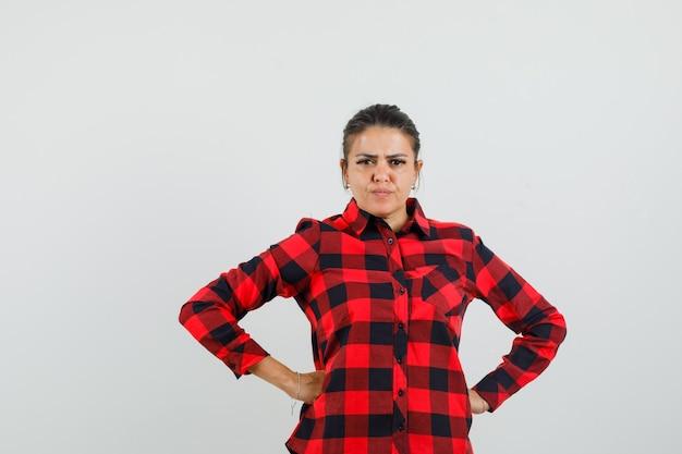 Młoda dama trzyma ręce na talii w kraciastej koszuli i wygląda poważnie.