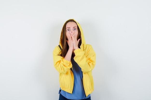 Młoda dama trzyma ręce na ustach w koszulce, kurtce i wygląda na przestraszoną