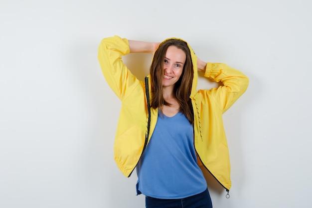 Młoda dama trzyma ręce za głową w koszulce, kurtce i wygląda uroczo