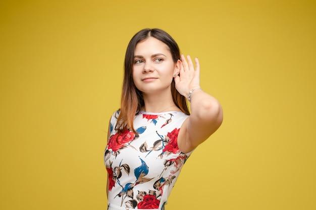 Młoda dama trzyma rękę blisko ucha i słucha ostrożnie