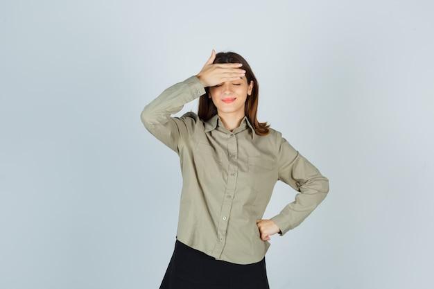 Młoda dama trzyma rękę na czole w koszuli, spódnicy i wygląda na zadowolonego