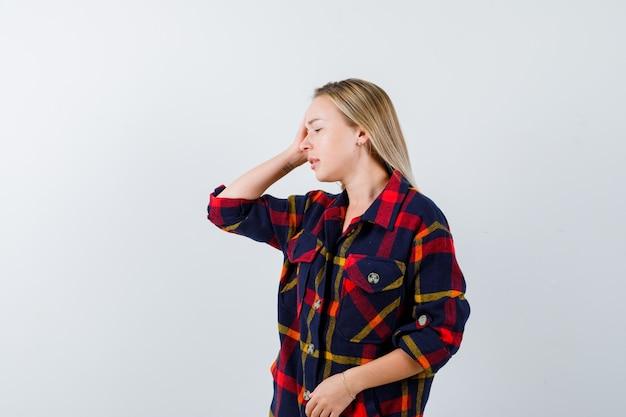 Młoda dama trzyma rękę na głowie, odwracając wzrok w kraciastej koszuli i patrząc zmęczony, widok z przodu.