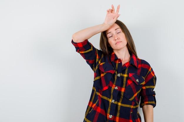 Młoda dama trzyma rękę na głowie w zwykłej koszuli i wygląda na wyczerpaną. przedni widok.