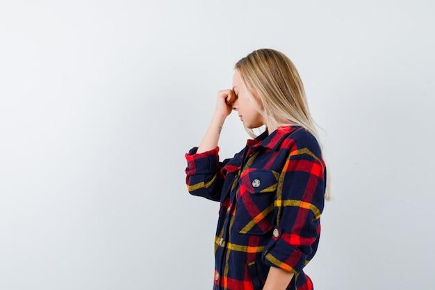 Młoda dama trzyma rękę na grzbiecie nosa w kraciastej koszuli i wygląda na zmęczoną. przedni widok.