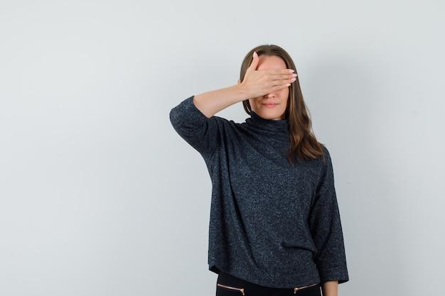 Młoda dama trzyma rękę na oczach w koszuli i wygląda optymistycznie