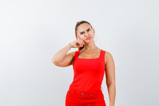 Młoda dama trzyma rękę na policzku w czerwonym podkoszulku, czerwonych spodniach i wygląda zamyślona. przedni widok.