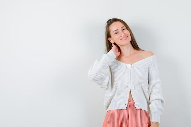Młoda dama trzyma rękę na szyi w swetrze i spódnicy, patrząc szczęśliwy na białym tle