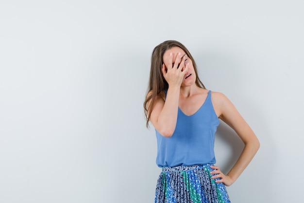 Młoda dama trzyma rękę na twarzy w bluzkę, spódnicę i wygląda na znudzoną, widok z przodu.