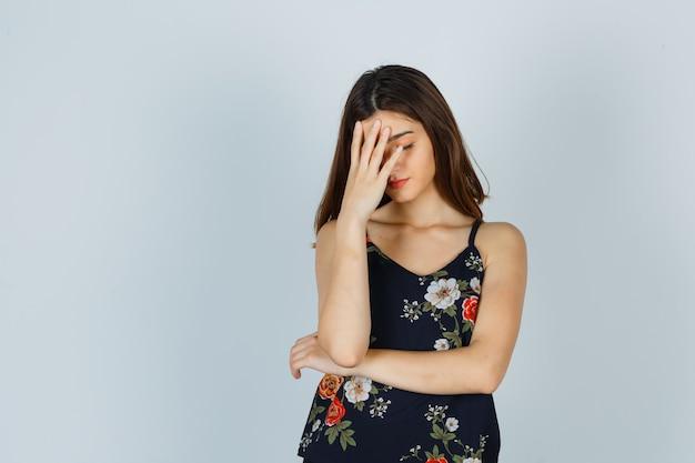 Młoda dama trzyma rękę na twarzy w kwiatowy top i wygląda na zmęczonego