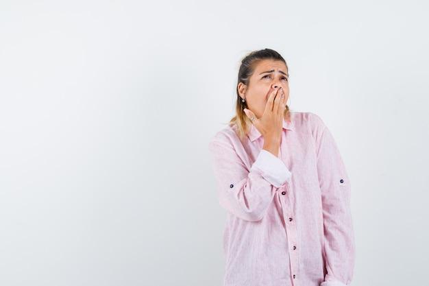 Młoda dama trzyma rękę na ustach podczas ziewania w różowej koszuli i wygląda śpiąco