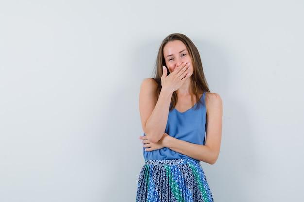 Młoda dama trzyma rękę na ustach w podkoszulku, spódnicy i pięknie wygląda