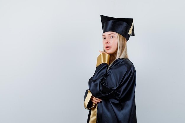 Młoda dama trzyma rękę pod brodą w akademickim stroju i wygląda atrakcyjnie.