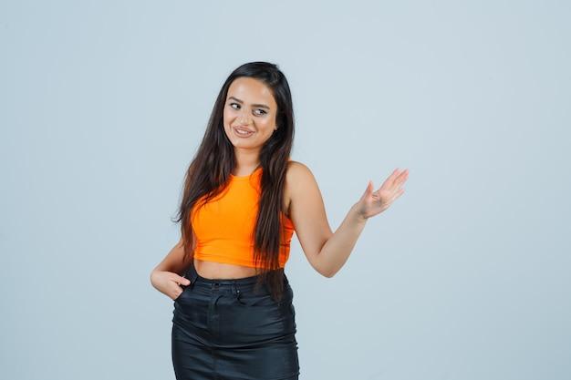 Młoda dama trzyma rękę w kieszeni i wita się w podkoszulku, mini spódniczce i wygląda atrakcyjnie, widok z przodu.