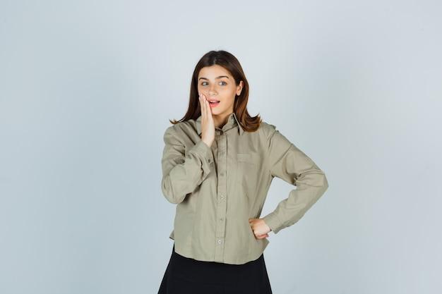 Młoda dama trzyma rękę w pobliżu ust w koszuli, spódnicy i zamyśleniu