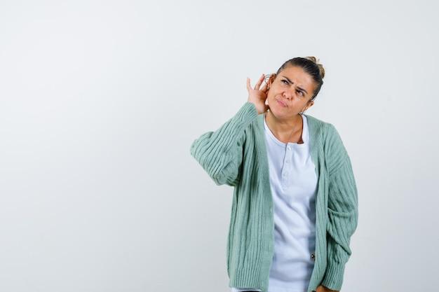 Młoda dama trzyma rękę za uchem w koszulce, kurtce i wygląda na pewną siebie