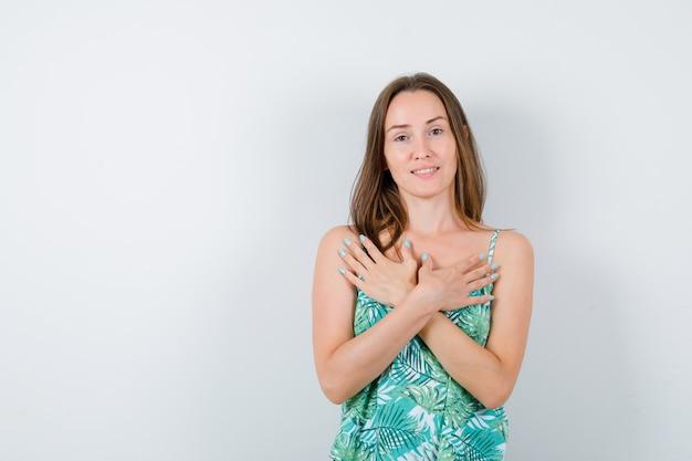 Młoda dama trzyma skrzyżowane ręce na klatce piersiowej i wygląda na szczęśliwą, widok z przodu.