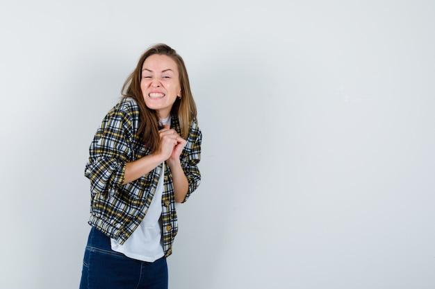 Młoda dama trzyma splecione dłonie na piersi w t-shirt, kurtce, dżinsach i wygląda na szczęśliwą, widok z przodu.