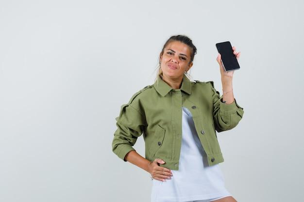 Młoda dama trzyma telefon komórkowy w koszulce, kurtce i wesoło. przedni widok.