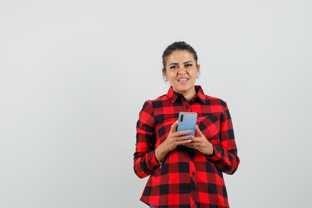 Młoda dama trzyma telefon komórkowy w kraciastej koszuli i wygląda pozytywnie