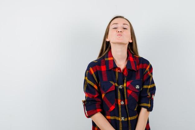 Młoda dama trzyma usta złożone w swobodnej koszuli i wygląda pięknie. przedni widok.